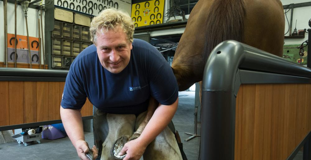 The German farrier Christoph Schweppe shoeing a horse