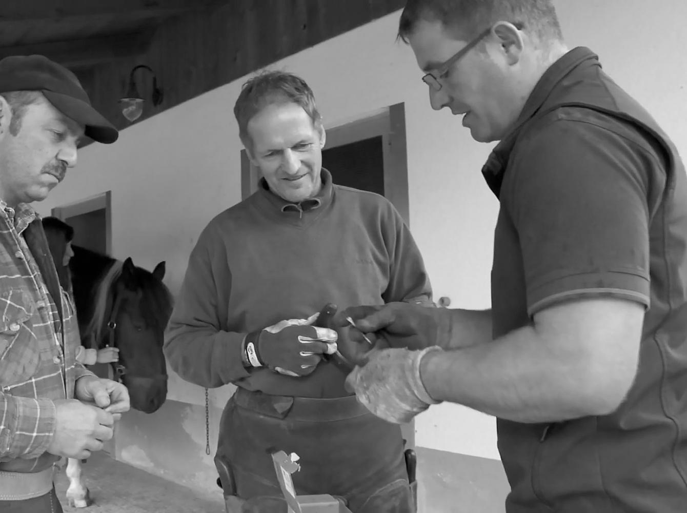 Christoph Müller talking with two farriers